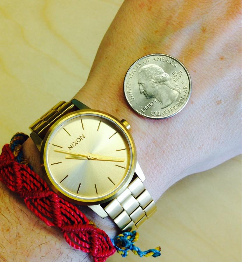Watch on wrist & next to a quarter